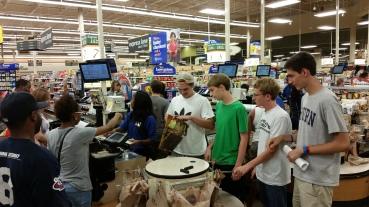 12th Grade Guys helping a stranger bag their groceries